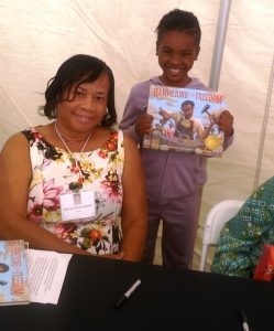 Image of Rita Hubbard with young fan holding book